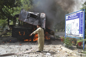 A firefighter stands near a burning bus after a bomb attack in Quetta