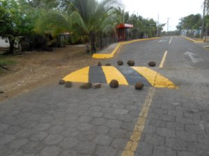 Third World problem solving.  How do you protect your freshly painted speed bump if you don't have traffic cones?  Just use big rocks.
