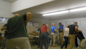 Students working at resisting forward pressure with weapons drawn