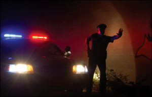 cop-in-front-of-cruiser-at-night