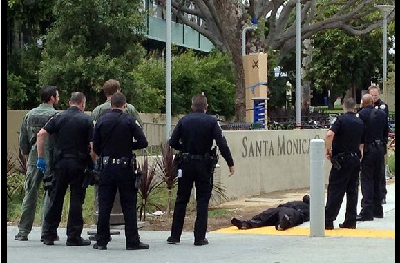 The killer dead on the sidewalk after cops drag him out of the library