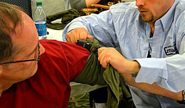 Student fashioning an improvised tourniquet with a triangular bandage and pistol magazine