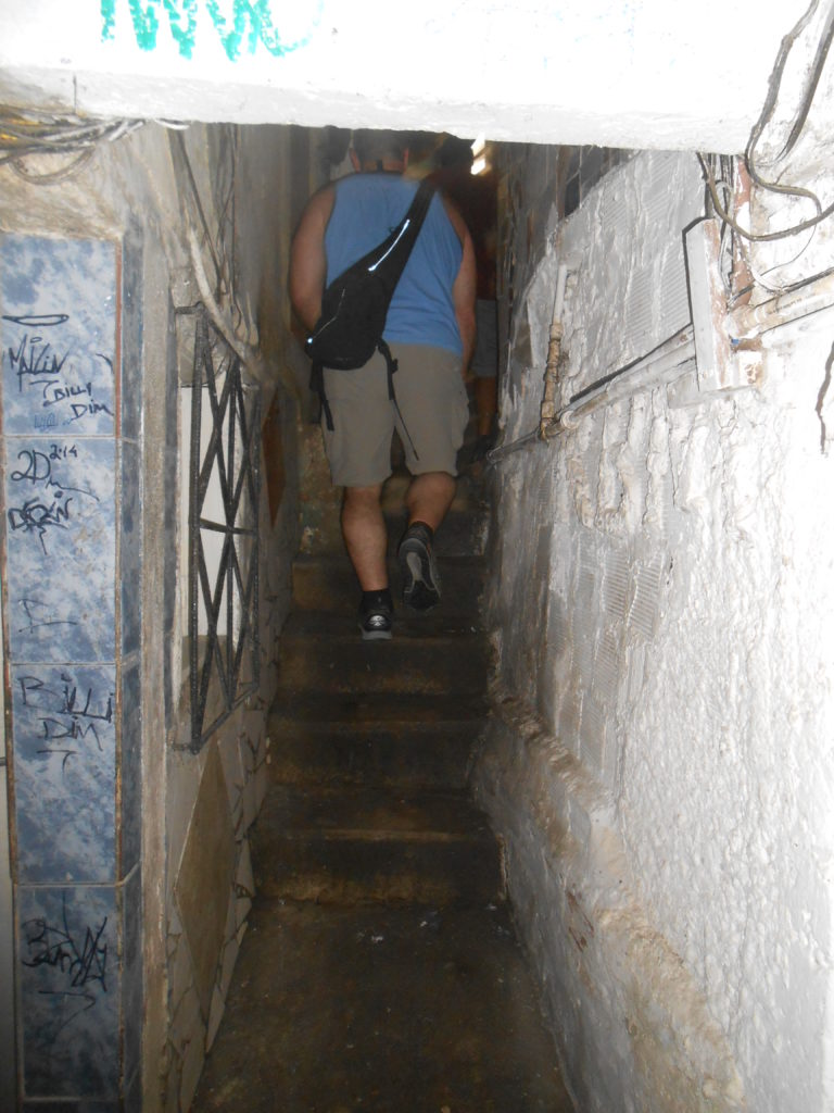 """Walking on a sidewalk between favela houses. Most favelas have no roads and residents walk in narrow passageways like this to get to their """"house."""""""