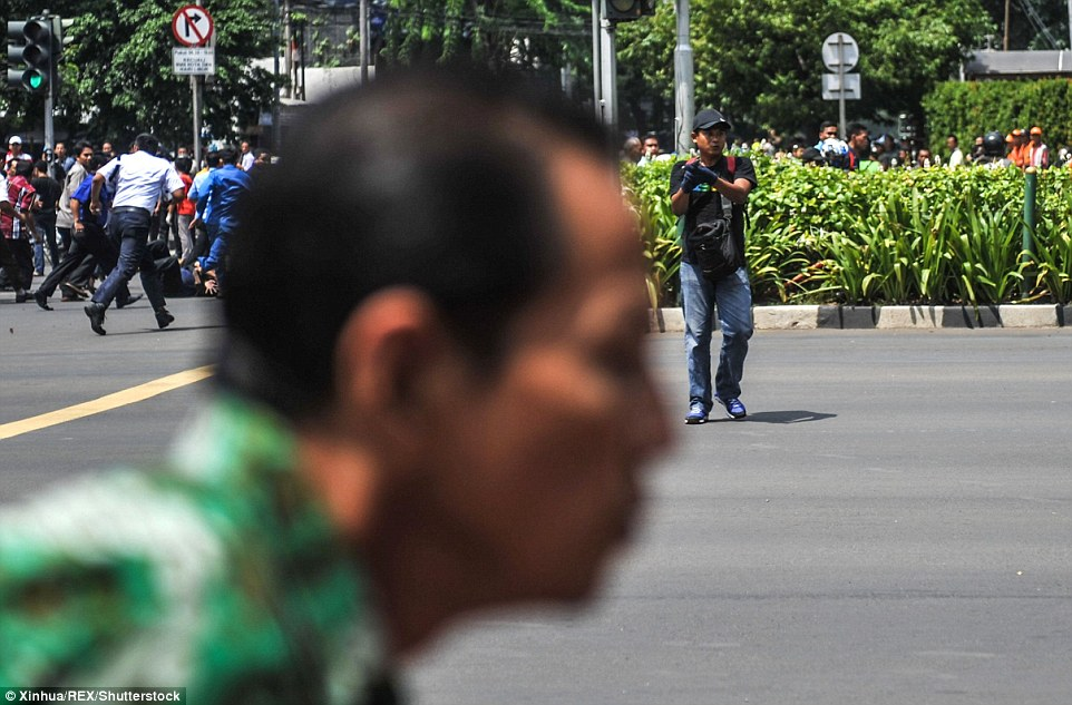 3027535E00000578-3398712-A_civilian_races_past_the_camera_as_hundreds_of_people_in_Jakart-m-23_1452755535141